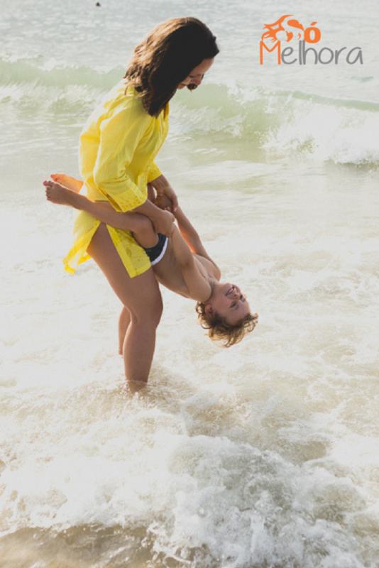 imagem de uma mãe brincando com seu filho no mar