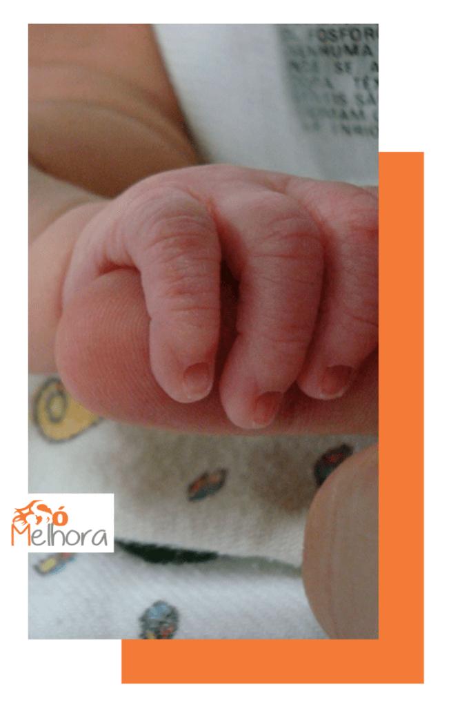 imagem da mãe de um bebê segurando o dedo da sua mãe