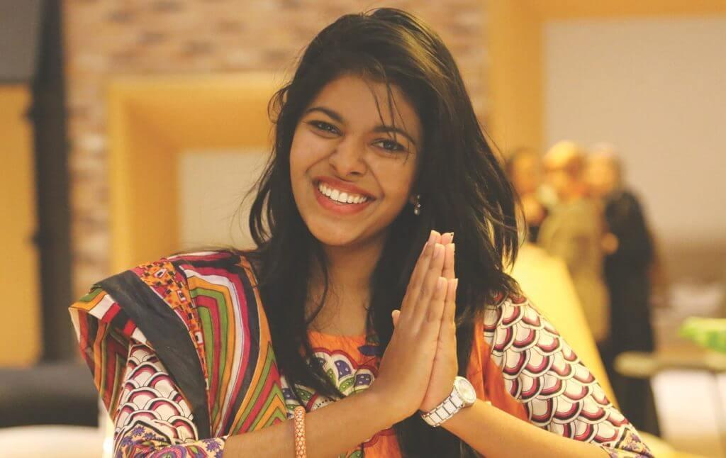 imagem de uma mulher sorrindo com as mãos juntas em oração