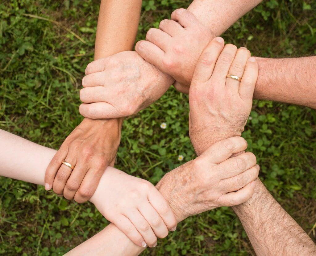 imagem de várias mãos entrelaçadas para exemplificar a convivência familiar e quarentena
