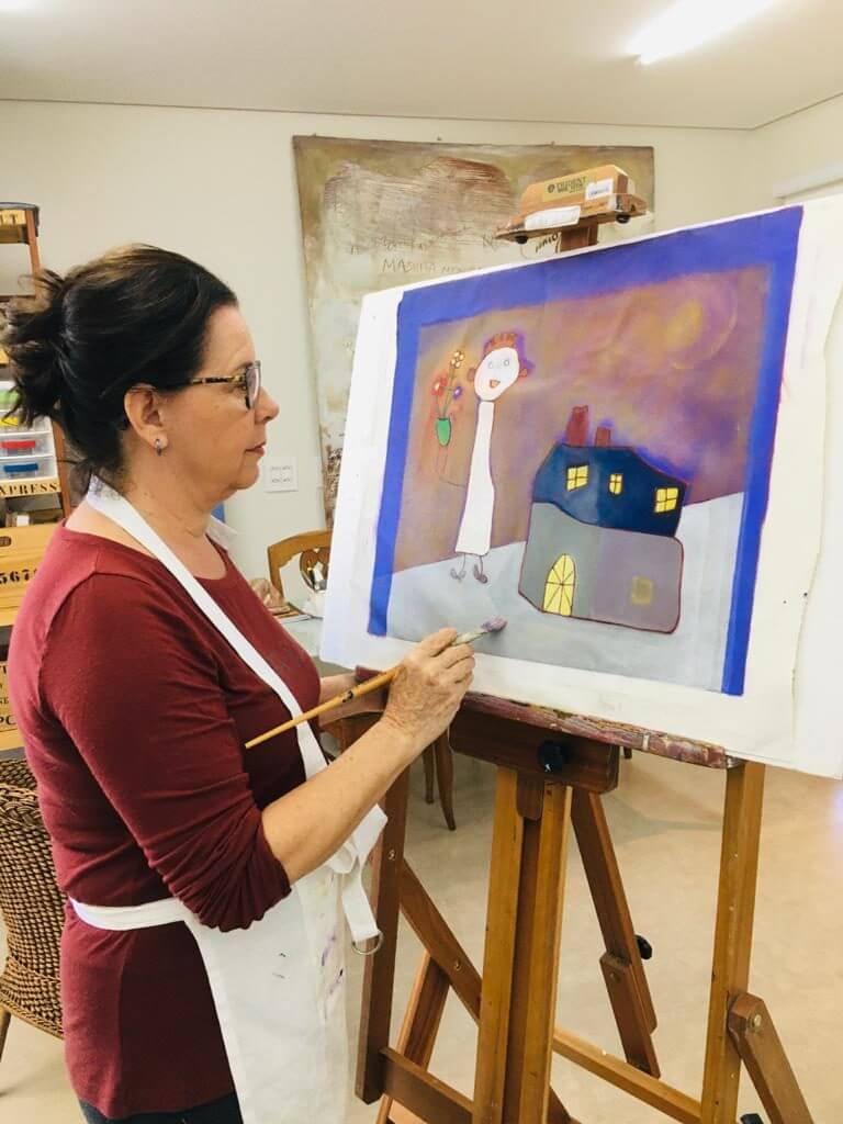 imagem de uma avó pintando um quadro inspirada nos desenhos dos netos