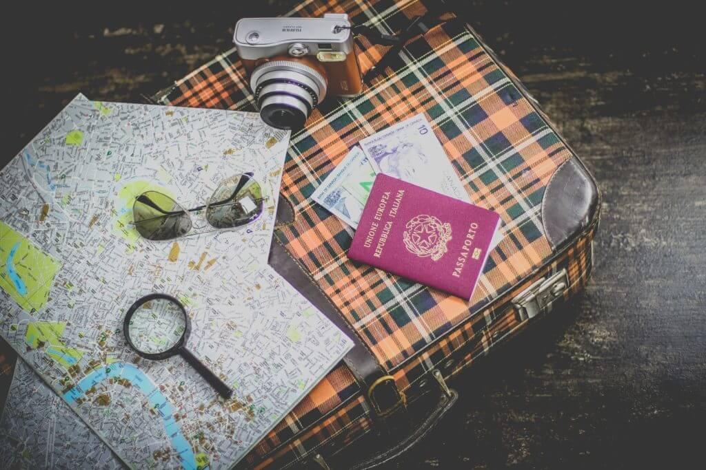 imagem de uma mala, mapa, passaporte, óculos, câmera fotográfica para exemplificar como economizar em sua viagem