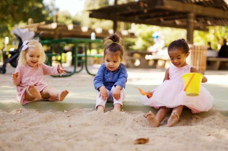 Imagem de 3 crianças brincando na areia