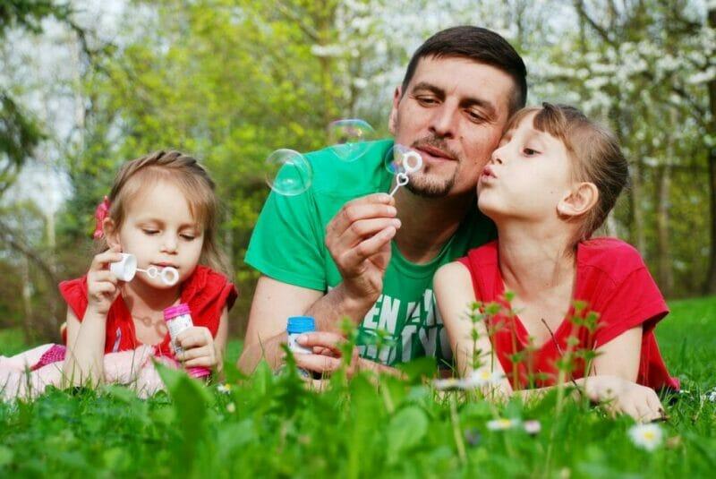 imagem de um pai com duas filhas para ilustrar o que fazer com o seu filho