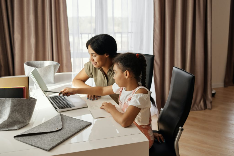 mãe ajudando a filha a fazer os deveres
