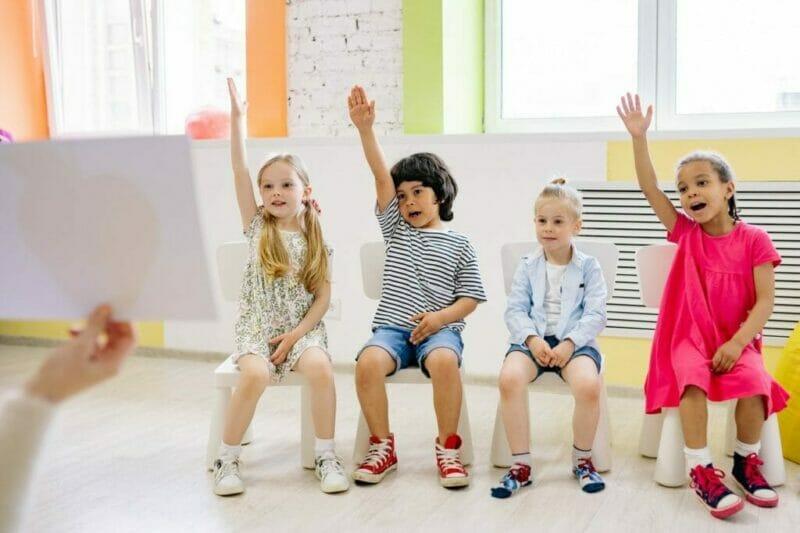 imagem de crianças levantando a mão para exemplificar atividade divertida para as crianças